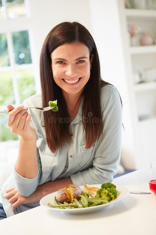 Portret van Vrouw die Gezonde Maaltijd in Keuken eten royalty-vrije stock afbeelding