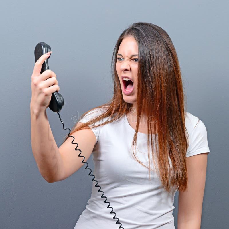 Portret van vrouw die onplezierig telefoongesprek hebben tegen grijze achtergrond stock afbeeldingen
