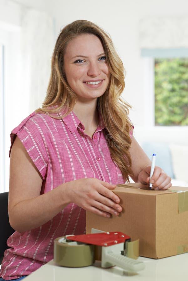 Portret van Vrouw die thuis Adres op Pakket schrijven stock foto