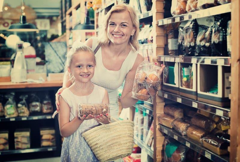 Portret van vrouw en meisjes graag het winkelen koekjes stock afbeeldingen