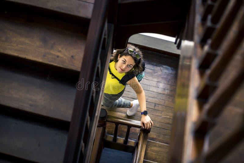 Portret van vrouw in geel overhemd die beneden en omhoog camera bekijken gaan royalty-vrije stock foto
