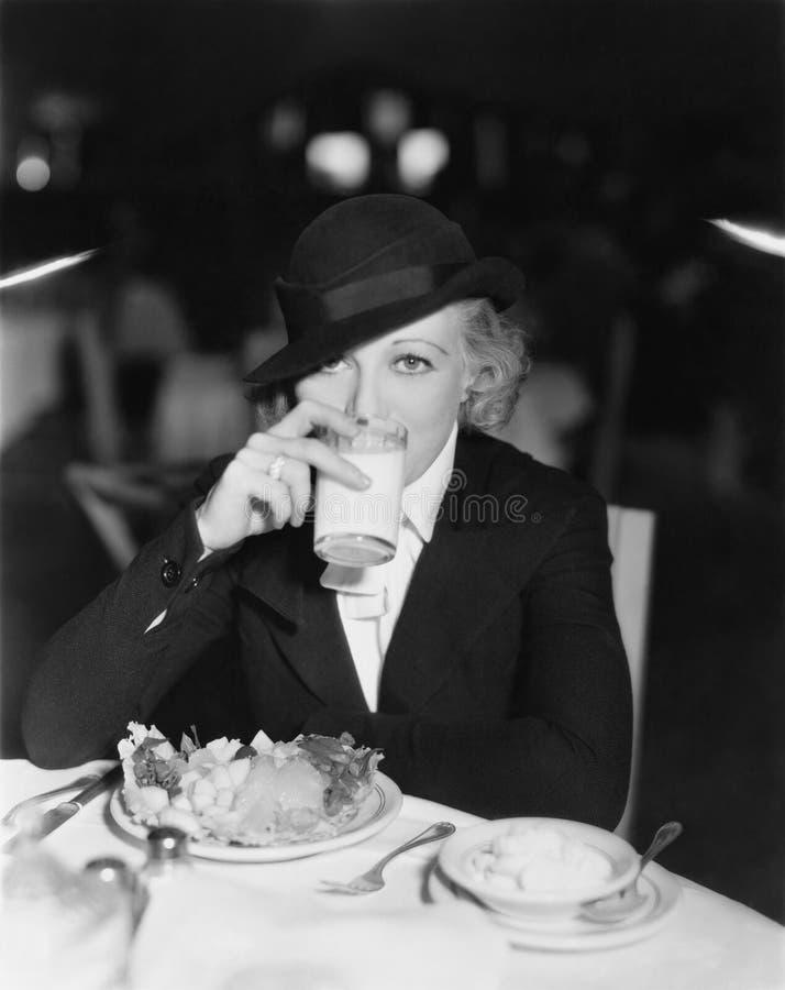 Portret van vrouw het drinken en het eten in restaurant (Alle afgeschilderde personen leven niet langer en geen landgoed bestaat  royalty-vrije stock foto's