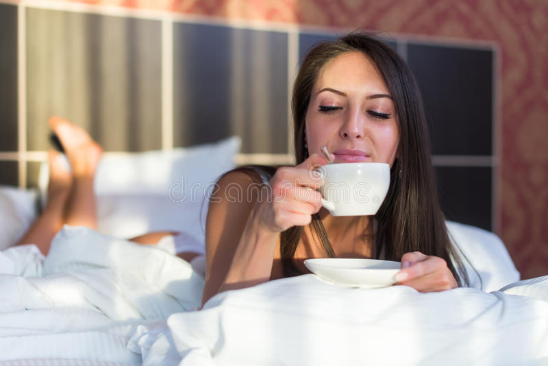 Portret van vrouw het drinken koffie in ochtendontwaken thuis stock fotografie