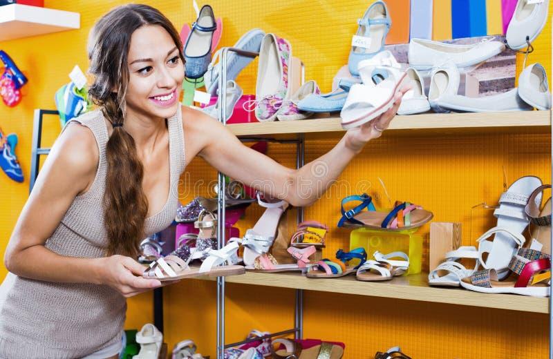 Portret van vrouw het kijken met twee paar schoenen wordt verward die royalty-vrije stock afbeelding