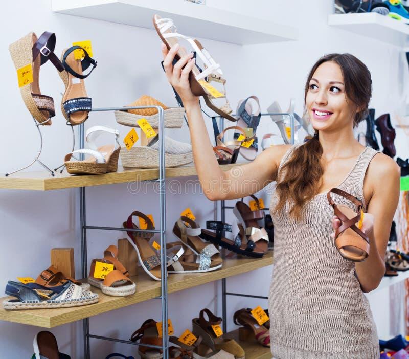 Portret van vrouw het kijken met twee paar schoenen wordt verward die stock fotografie