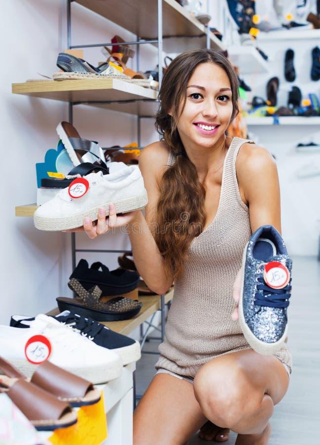 Portret van vrouw het kijken met twee paar schoenen wordt verward die stock foto's