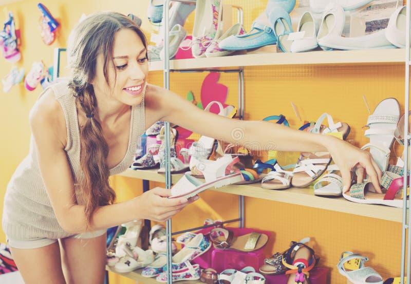 Portret van vrouw het kijken met twee paar schoenen wordt verward die royalty-vrije stock foto's