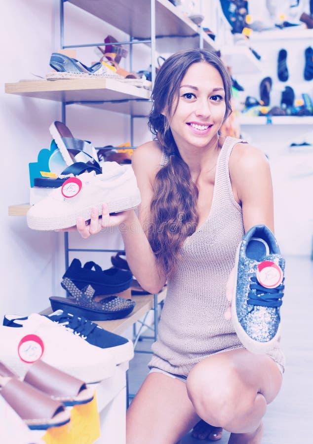 Portret van vrouw het kijken met twee paar schoenen wordt verward die stock afbeelding