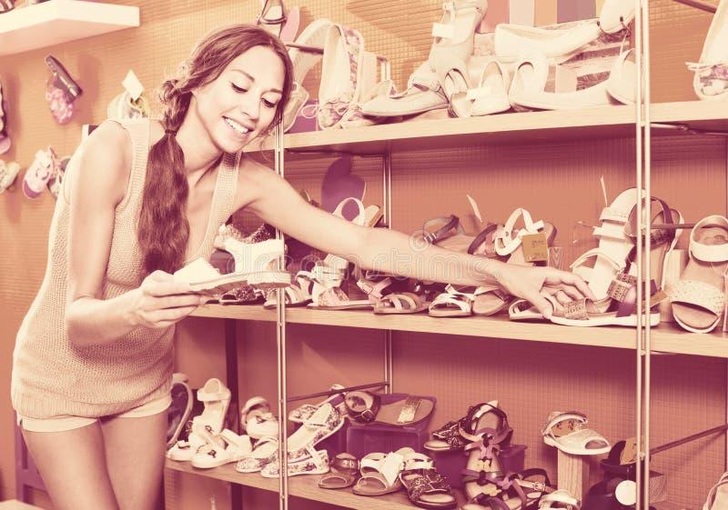 Portret van vrouw het kijken met twee paar schoenen wordt verward die stock foto