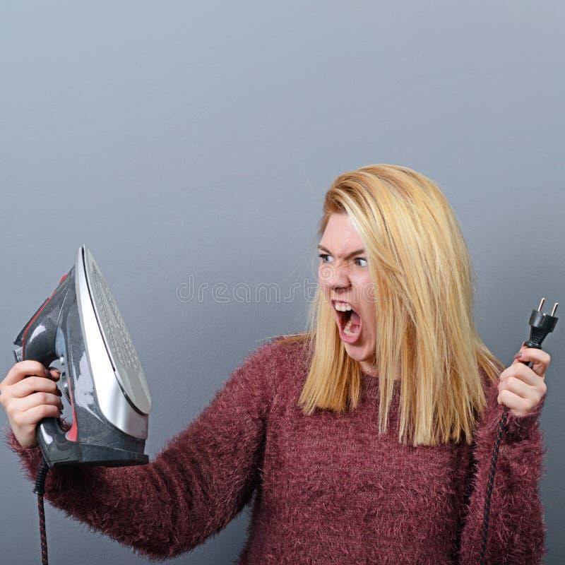 Portret van vrouw het schreeuwen bij ijzer en vermoeid van het huiswerk tegen grijze achtergrond stock fotografie