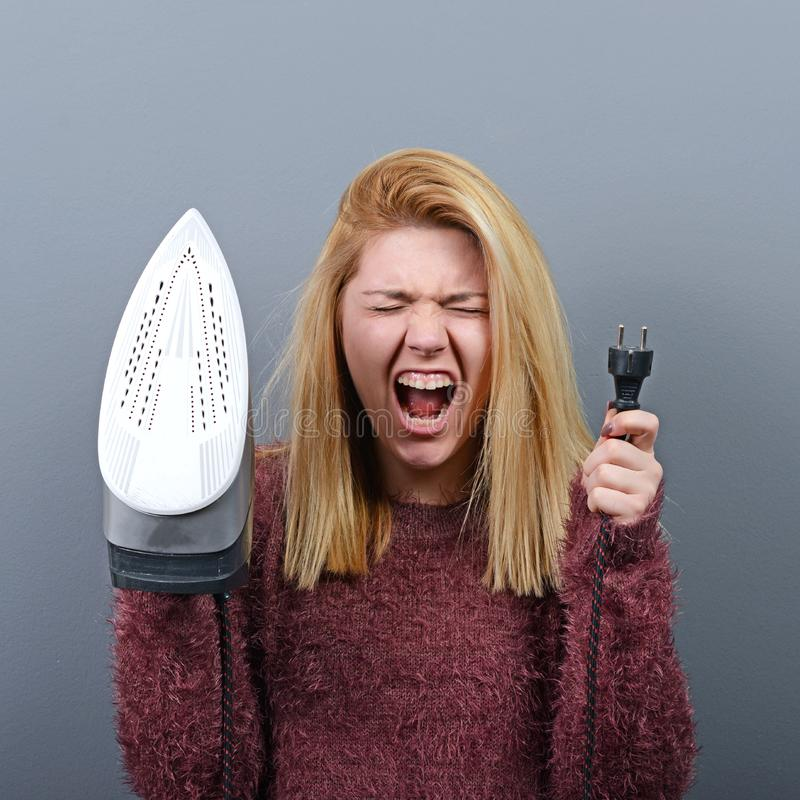 Portret van vrouw het schreeuwen bij ijzer en vermoeid van het huiswerk tegen grijze achtergrond royalty-vrije stock foto