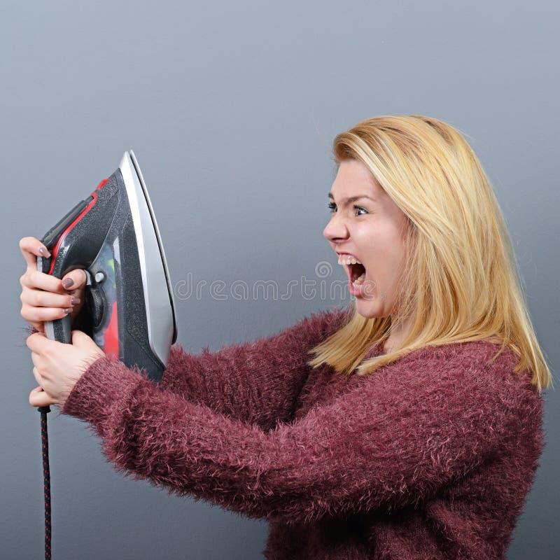 Portret van vrouw het schreeuwen bij ijzer en vermoeid van het huiswerk tegen grijze achtergrond stock foto's