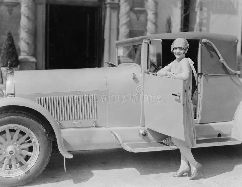 Portret van vrouw het stellen met auto stock fotografie