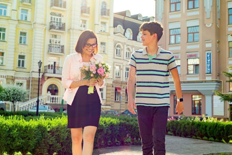 Portret van vrouw met boeketten van bloemen en tiener op stadsachtergrond De zoon wenste zijn moeder geluk royalty-vrije stock afbeeldingen