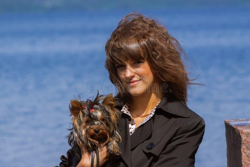 Portret van vrouw met de krullende hond van Yorkshire Terrier van de haarholding royalty-vrije stock foto's