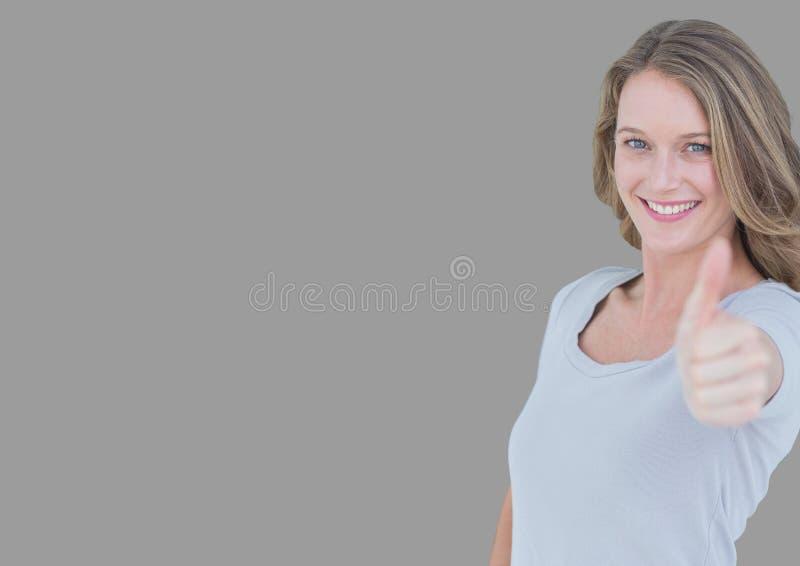 Portret van vrouw met duimen omhoog met grijze achtergrond stock afbeelding