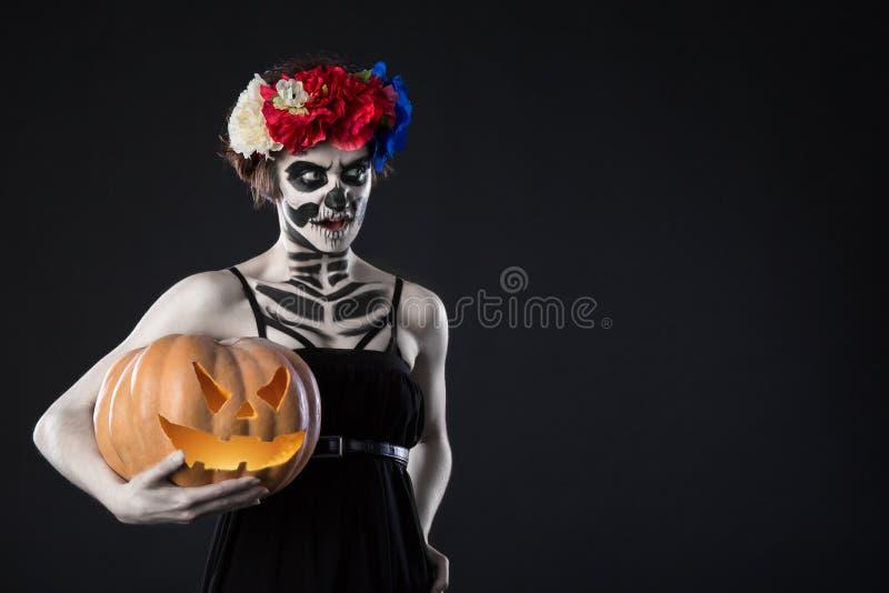 Portret van vrouw met kroon en enge Halloween-make-up Zombii in kroon met pompoen over zwarte achtergrond royalty-vrije stock foto