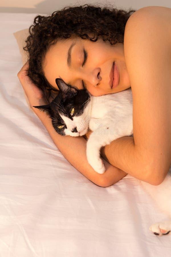 Portret van vrouw met krullende haarslaap met haar zwart-witte kat in bed Concept liefde aan dieren, huisdieren, zorg, royalty-vrije stock foto