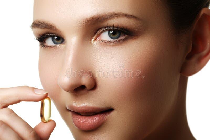 Portret van vrouw met Omega 3 vistraancapsule, in openlucht Voedsel stock afbeelding