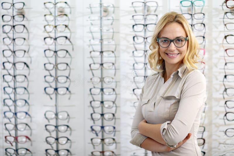 Portret van vrouw met oogglazen in eyewear winkel stock afbeeldingen