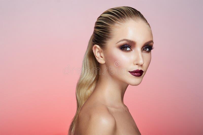 Portret van vrouw met schitterende make-up en haar dat in de rug wordt rechtgemaakt en wordt gevangen, die op een roze achtergron stock afbeeldingen