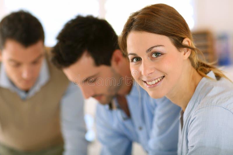 Portret van vrouw met team die zich in bureau bevinden stock afbeeldingen