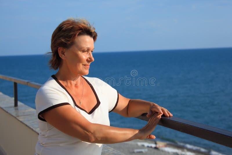Portret van vrouw op middelbare leeftijd op balkon over overzees royalty-vrije stock foto