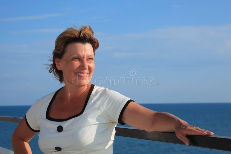 Portret van vrouw op middelbare leeftijd op balkon over overzees stock fotografie