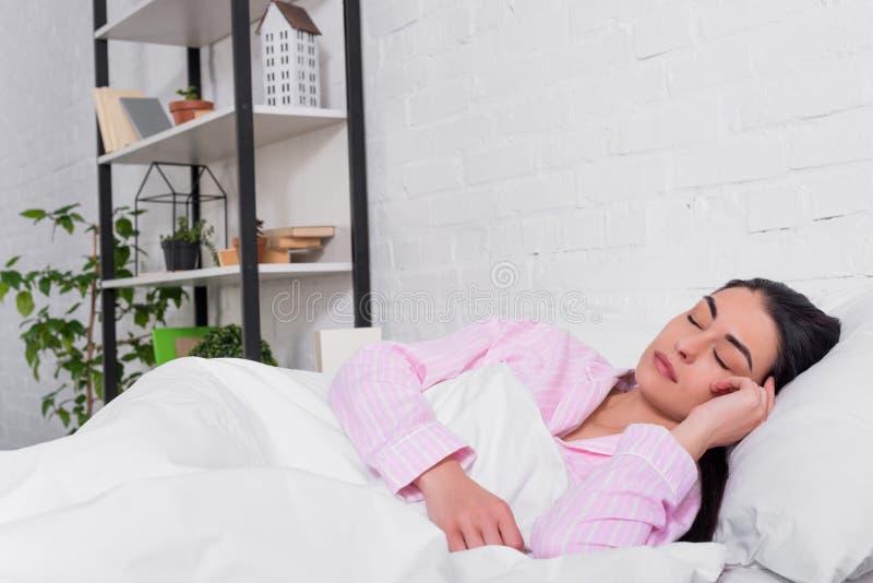 portret van vrouw in roze pyjama's die in bed slapen royalty-vrije stock afbeeldingen