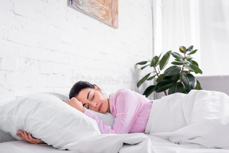 portret van vrouw in roze pyjama's die in bed slapen stock foto's