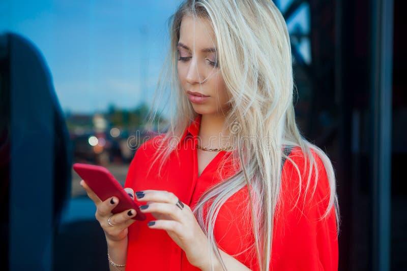 Portret van vrouw van het schoonheids de glimlachende blonde in rood overhemd die smartphone gebruiken dichtbij het bureau Exempl royalty-vrije stock afbeeldingen