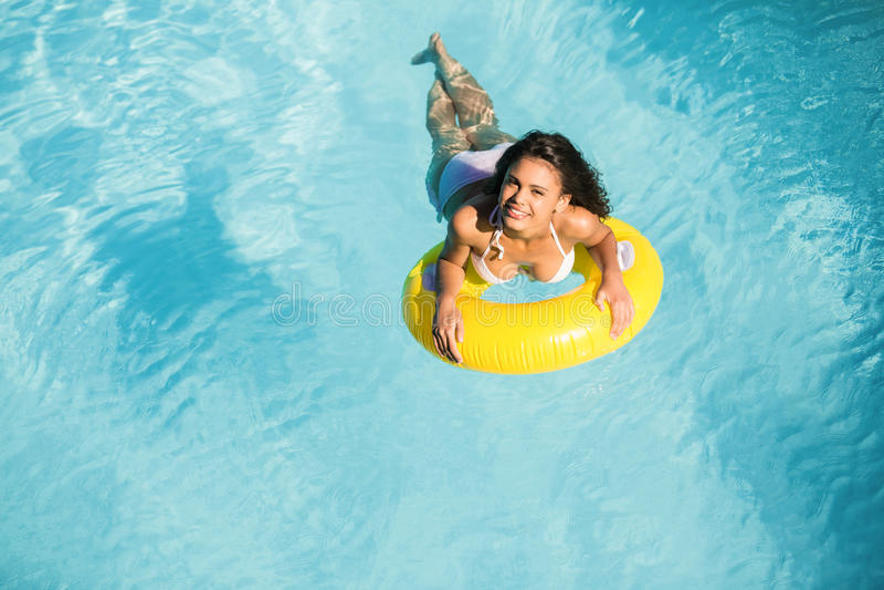 Portret van vrouw in witte bikini die op opblaasbare buis in zwembad drijven royalty-vrije stock fotografie