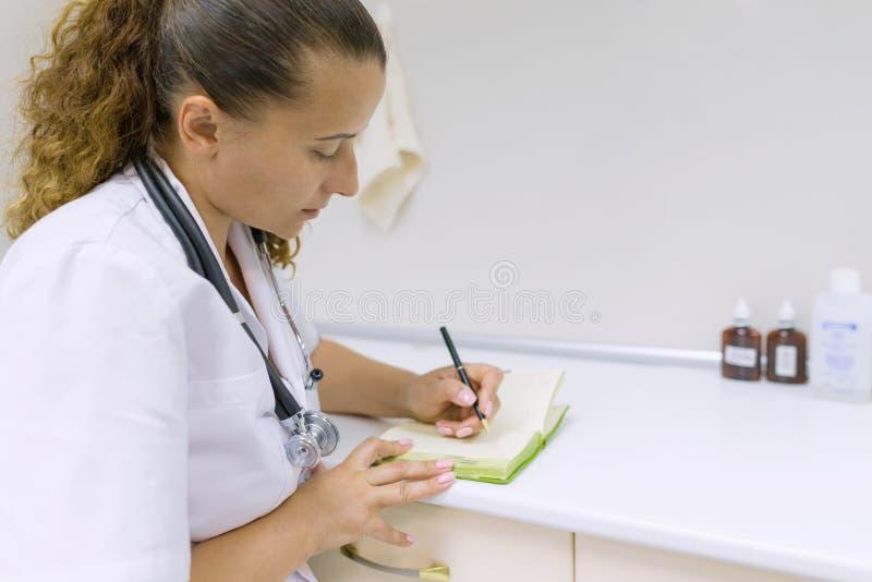Portret van vrouwelijke arts in het ziekenhuiszitting bij lijst met pen en notitieboekje royalty-vrije stock afbeeldingen