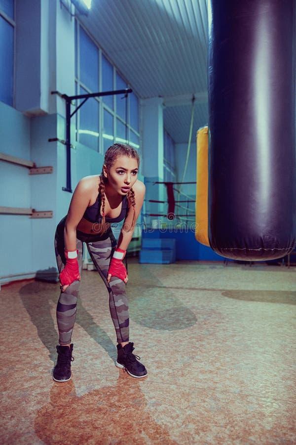 Portret van vrouwelijke bokser in sportslijtage met het vechten houding tegen schijnwerper Sexy fitness blondemeisje in sportslij royalty-vrije stock fotografie