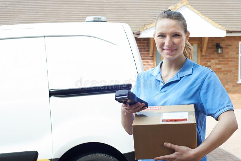Portret van Vrouwelijke Koerier With Van Delivering Package To House stock foto's