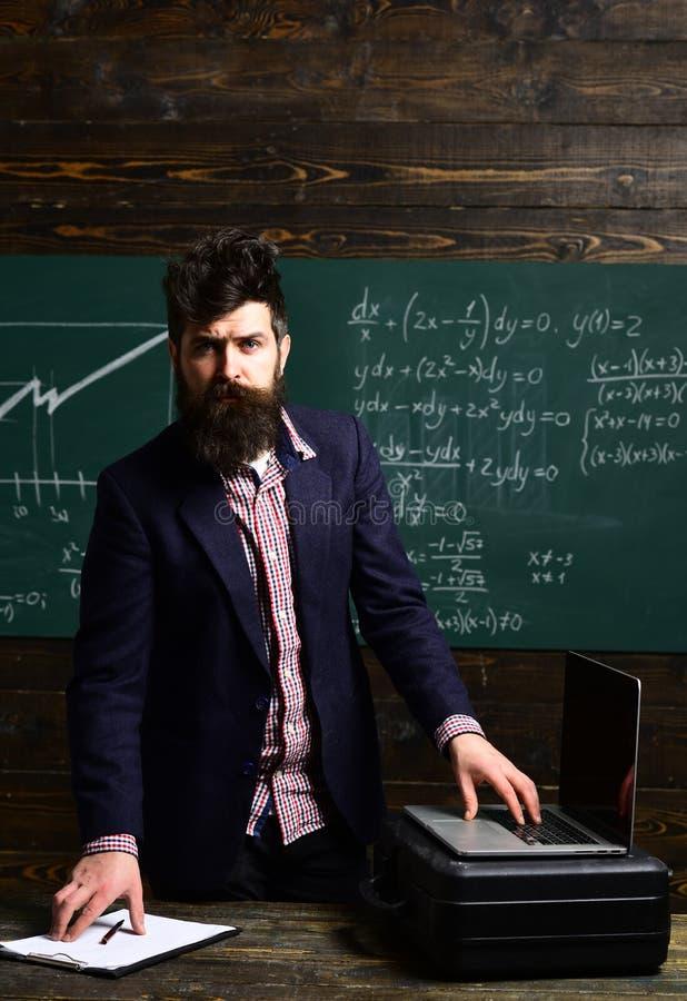 Portret van vrouwelijke leraar die moderne technologielaptop in haar klasse met behulp van Privé-leraarzitting naast bureau tijde stock foto's