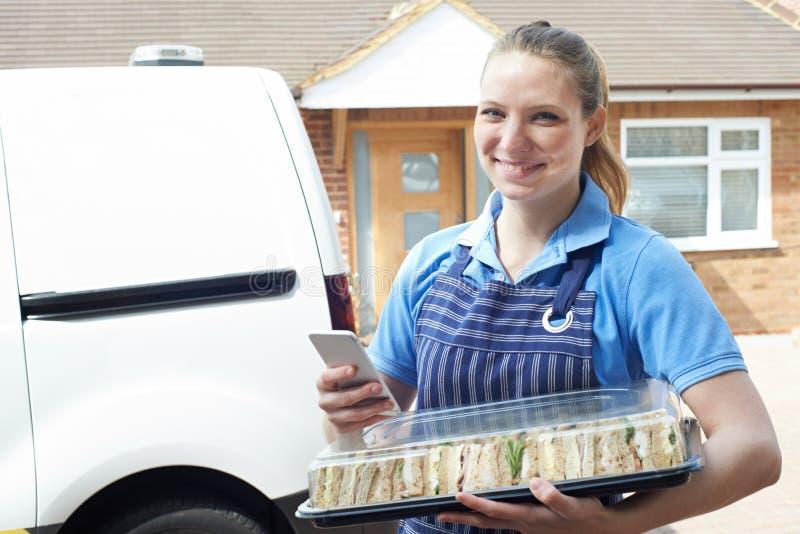 Portret van Vrouwelijke Traiteur die Mobiele Telefoon met behulp van die Tray Of Sandwiches To House leveren stock fotografie