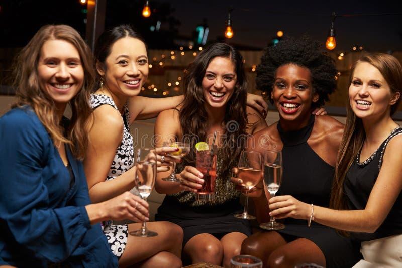 Portret van Vrouwelijke Vrienden die van Nacht genieten uit bij Dakbar royalty-vrije stock foto