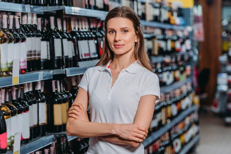 portret van vrouwelijke winkelmedewerker met gekruiste wapens het bekijken camera stock foto