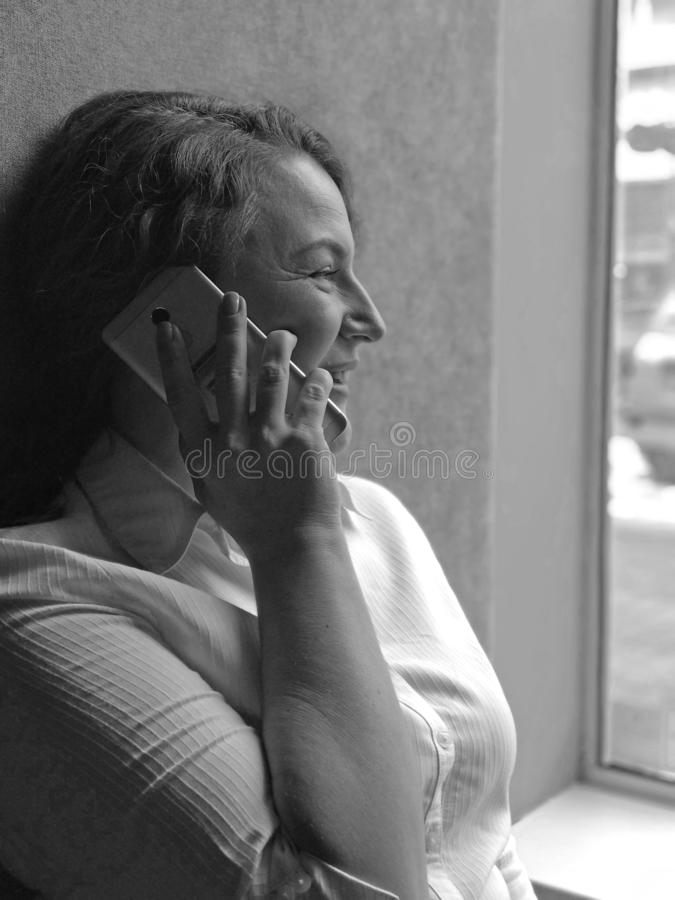 Portret van vrouwenbesprekingen op de telefoon en het kijken aan venster stock foto