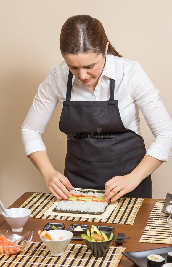 Portret van vrouwenchef-kok die een Japanse sushi oprollen royalty-vrije stock afbeeldingen