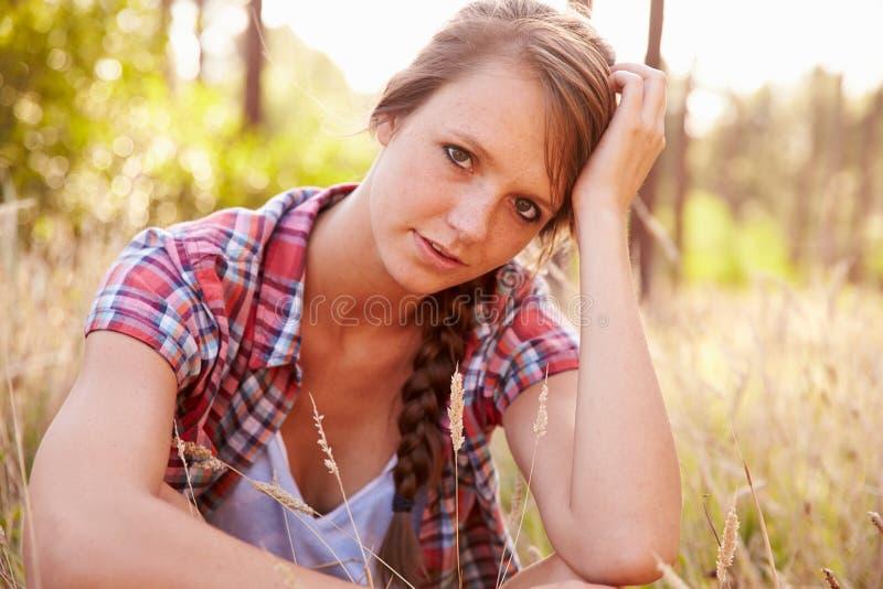 Portret van Vrouwenzitting in Platteland op Gebied van Gras royalty-vrije stock fotografie