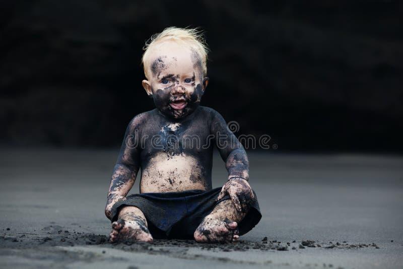 Portret van vuil kind op het zwarte San-strand stock afbeelding