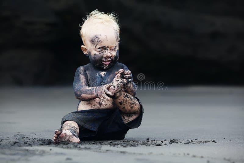 Portret van vuil kind op het zwarte San-strand royalty-vrije stock afbeelding