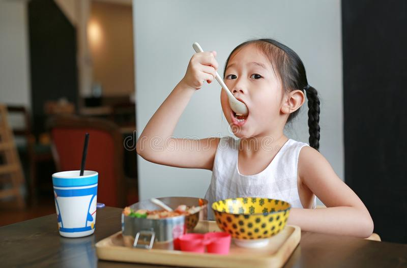 Portret van weinig Aziatisch kindmeisje die ontbijt hebben bij de ochtend royalty-vrije stock afbeeldingen