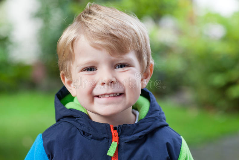Portret van weinig blonde peuterjongen die in openlucht glimlacht royalty-vrije stock fotografie
