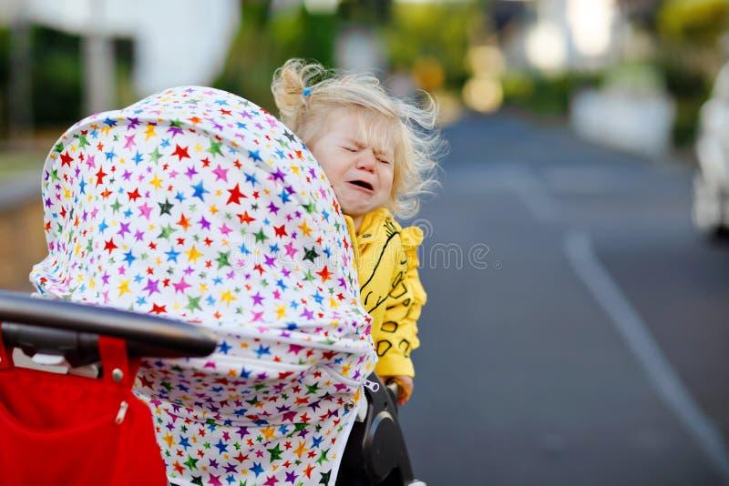 Portret van weinig droevige zitting van het peutermeisje in wandelwagen en het gaan voor een gang Het schreeuwende babykind wil n stock fotografie