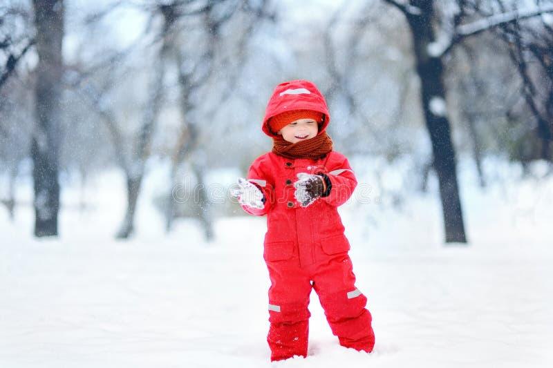 Portret van weinig grappige jongen in rode de winterkleren die pret met sneeuw hebben tijdens sneeuwval stock afbeelding