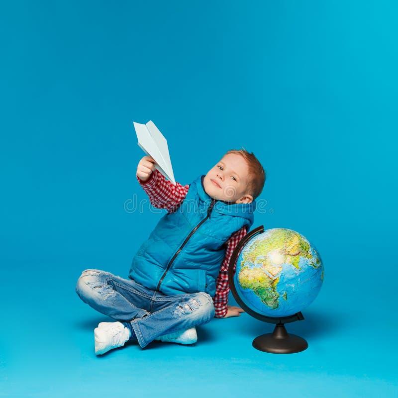 Portret van weinig grappige schooljongen met stuk speelgoed document vliegtuig Het tonen van plaats op de bol, kaart Conceptenrei royalty-vrije stock fotografie