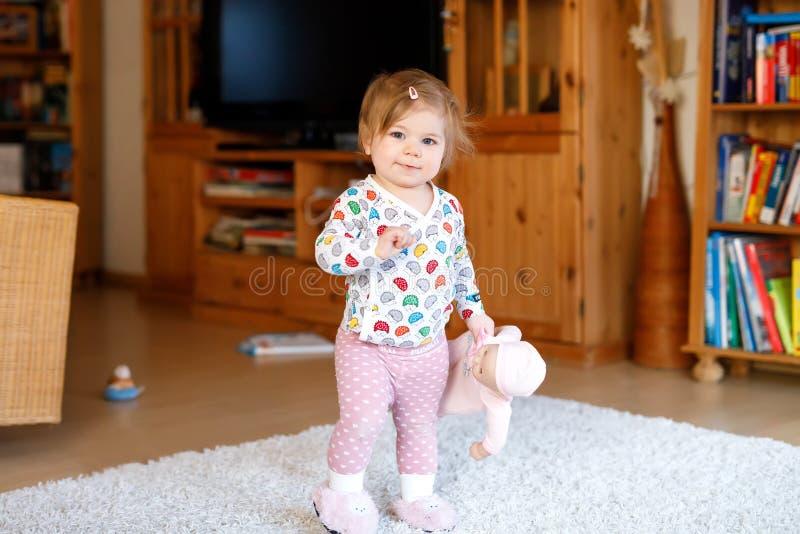 Portret van weinig het leuke babymeisje leren lopend en zich bevindt Aanbiddelijk peutermeisje thuis stock foto's